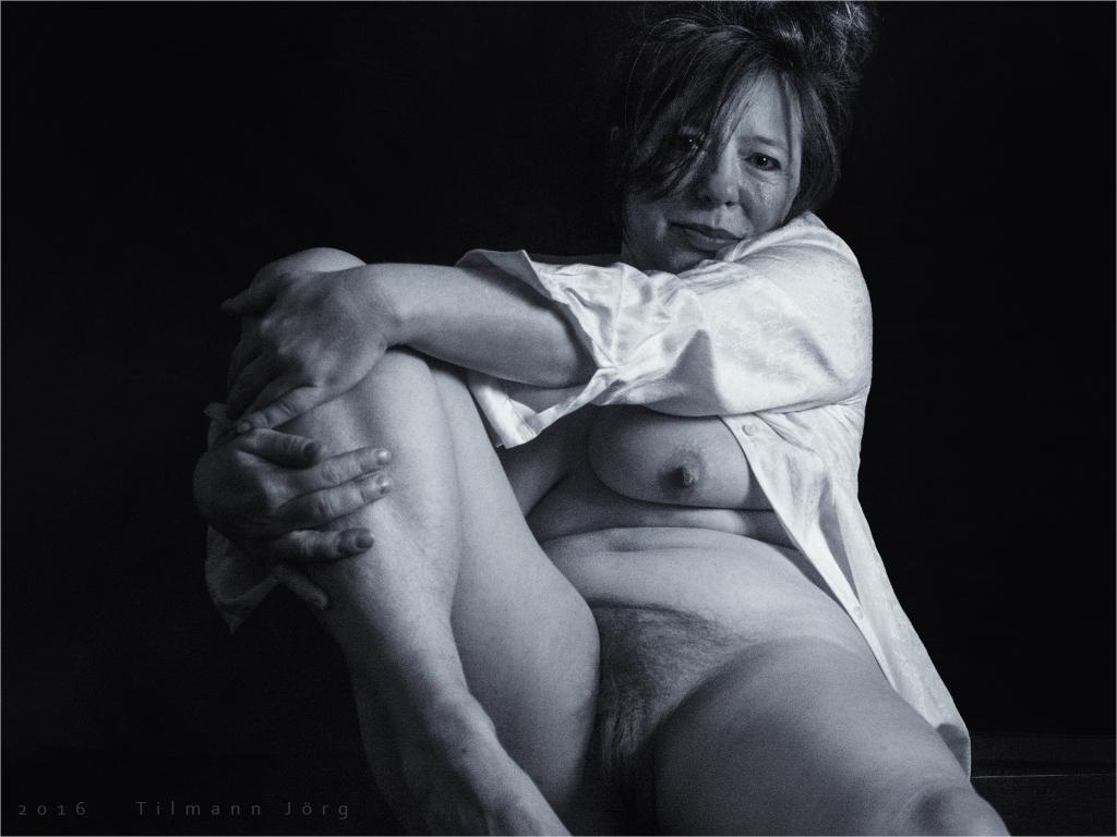 halbnackte Frau liegt auf dem Boden und guckt indifferent