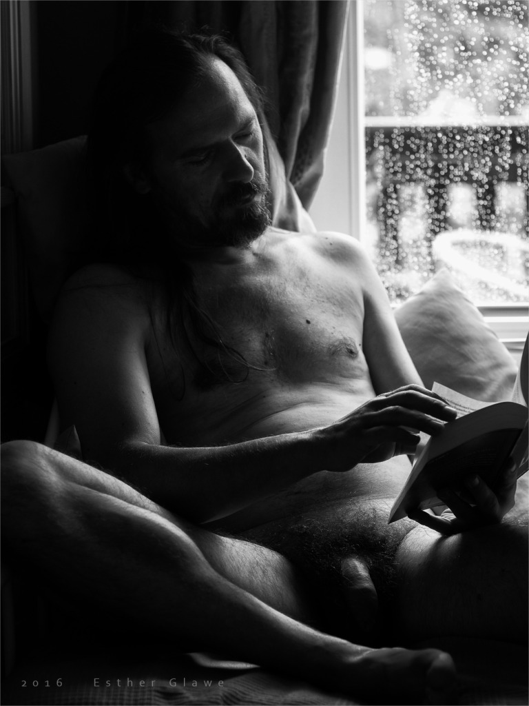 nackter Mann liest in einem Buch