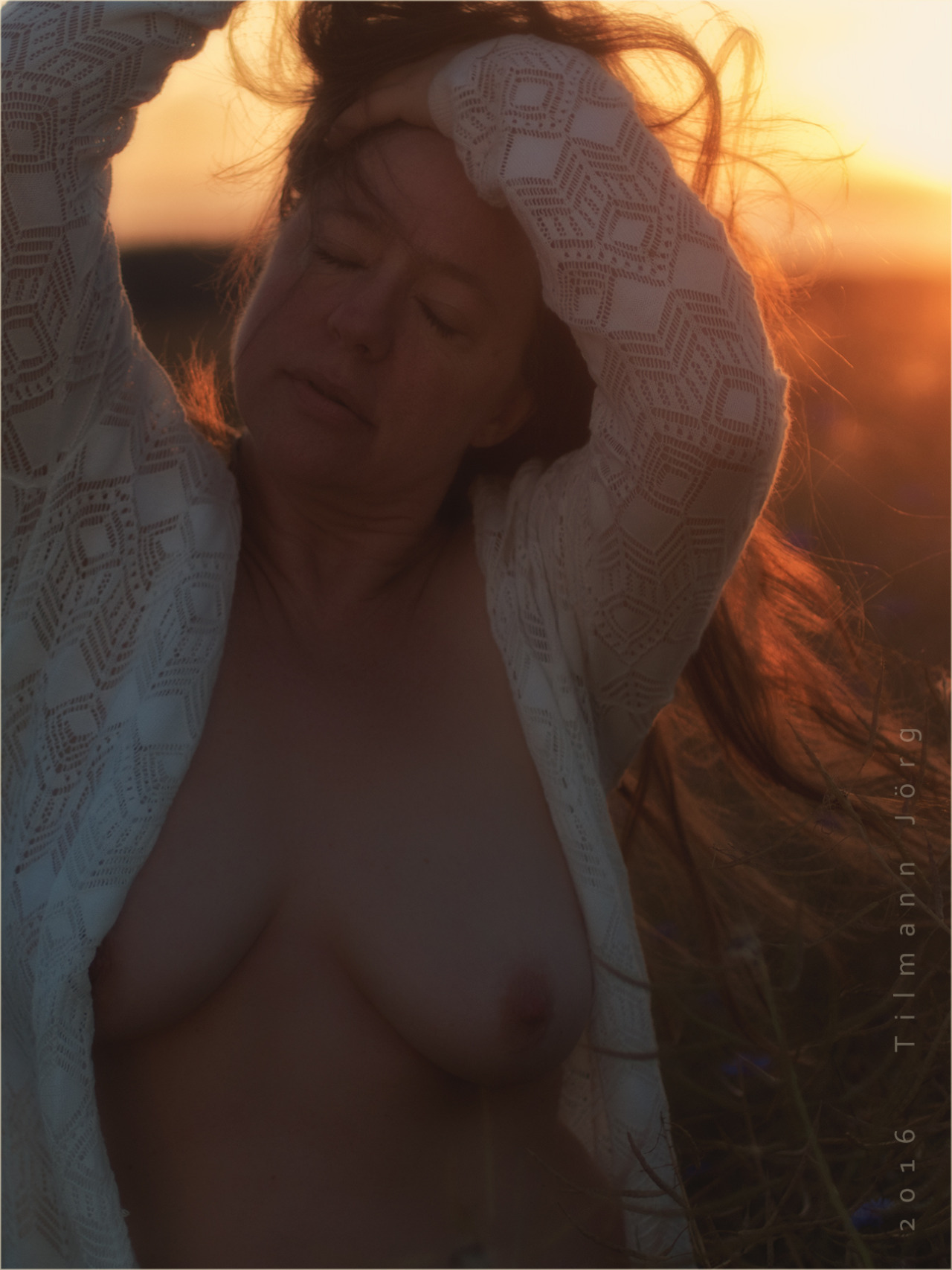 halbnackte Frau vor einem Sonnenuntergang