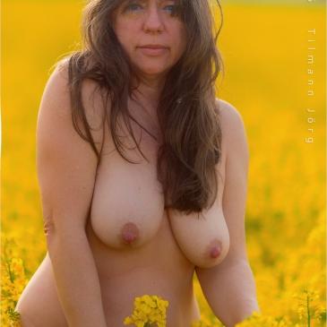 nackte Frau in einem Rapsfeld in voller Blüte