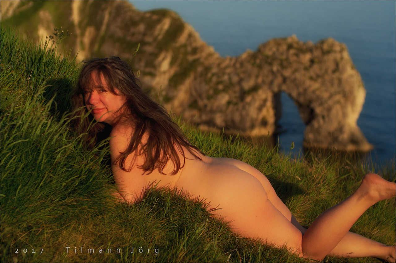 nackte Frau liegt vor dem Durdle Door