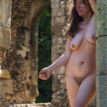 Nackte Frau inmitten einer mittelalterlichen Klosterruine