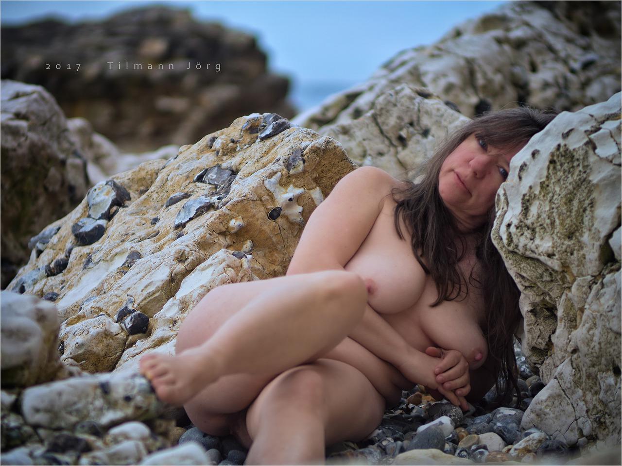 nackt frau liegt am strand der englischen kreideküste