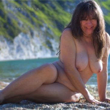 nackte Frau liegt am Strand