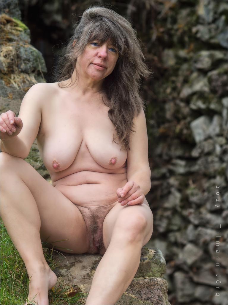 nackte frau sitzt auf einer steinmauer