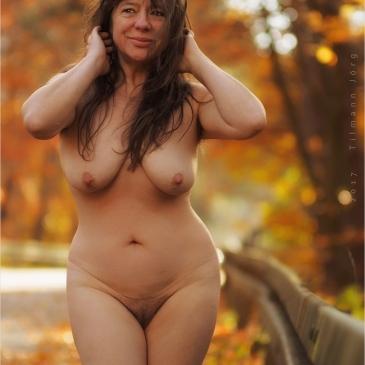 nackte Frau steht auf herbstlicher Straße