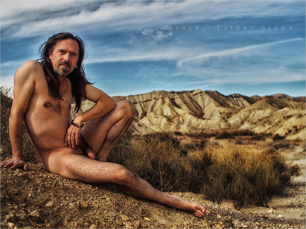 nackter Mann sintz in der Wüste