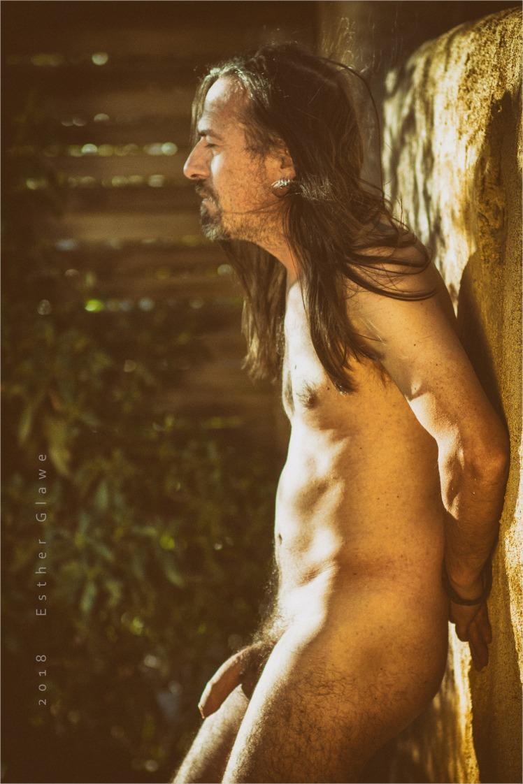nackter mann im garten lehnt an einer Mauer