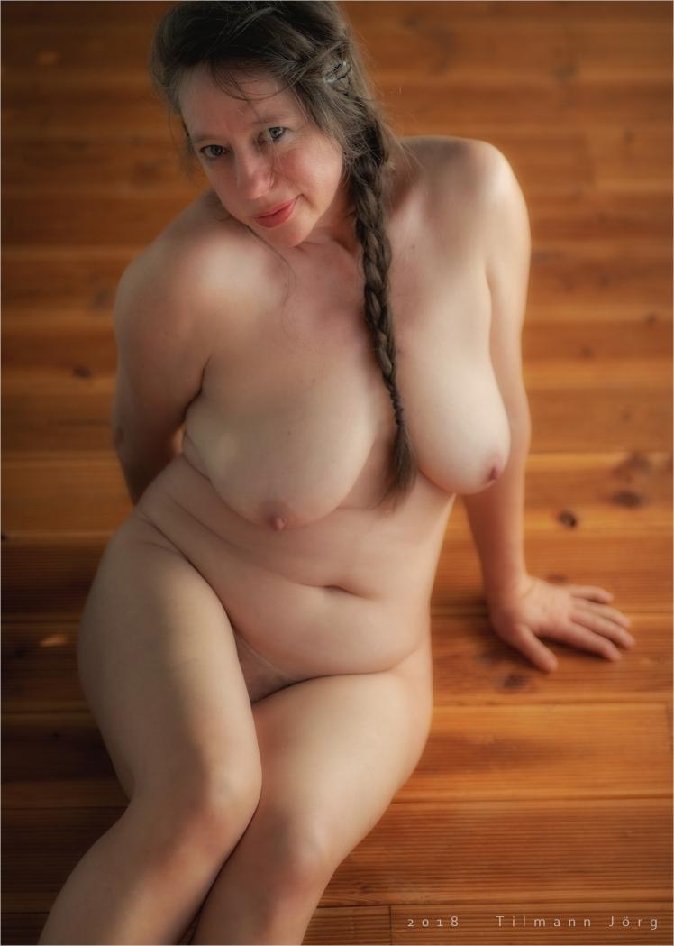 nackte frau sitzt auf dem Holzfußboden