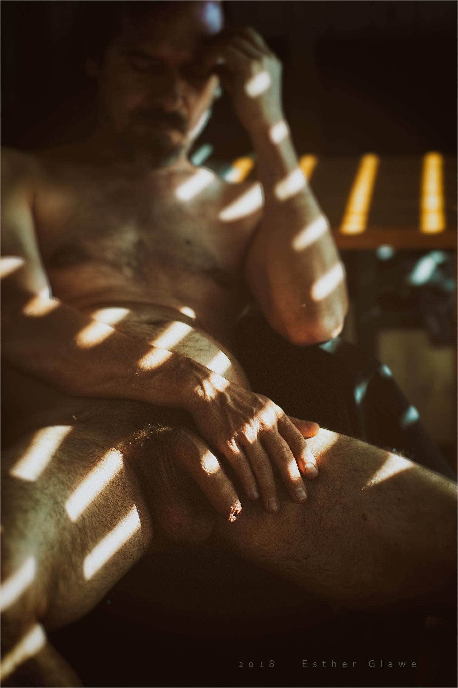 Nackter mann sitzt im Halbdunklen