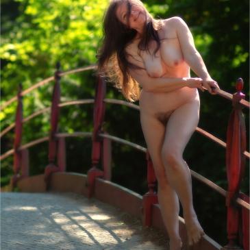 Nackte Frau steht auf Brücke
