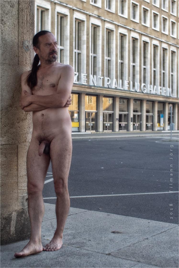 Nackter Mann vor Flughafen