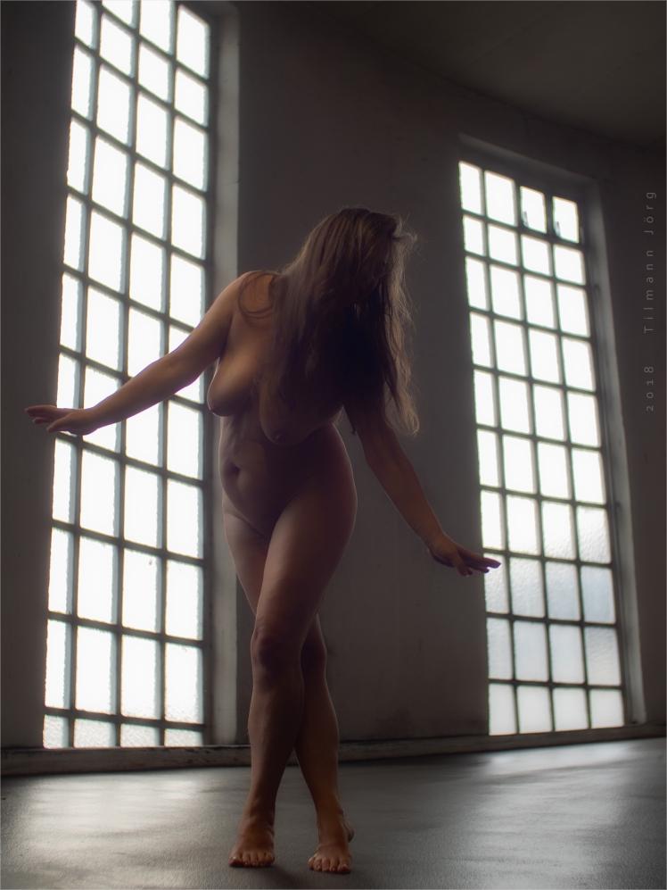 Nackte Frau vor Parkhausfenstern