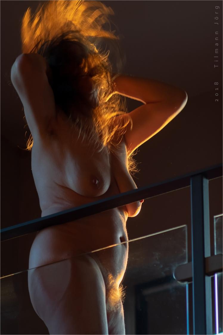 Nackte Frau auf Balustrade in moderner Wohnung