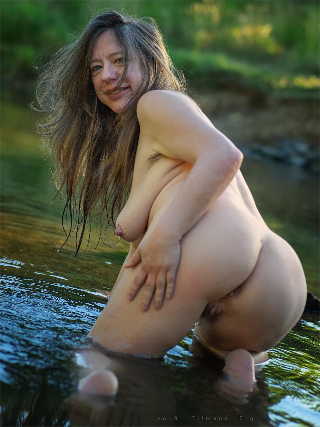 Nackte Frau kniet in seichtem Wasser