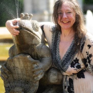Frau plantscht im Brunnen
