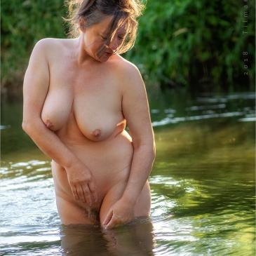 nackte frau badet im fluss