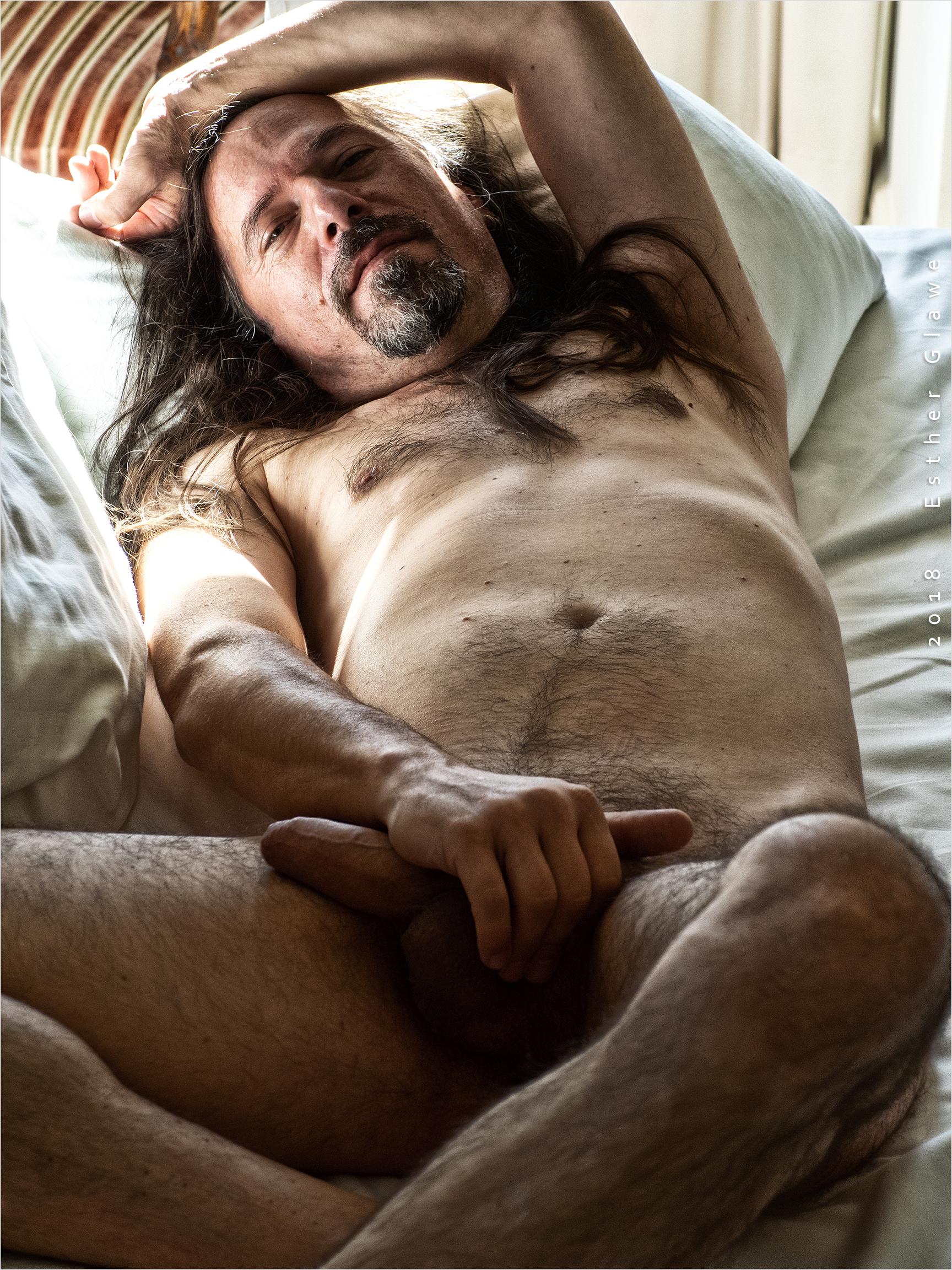 nackter Mann liegt auf dem Bett
