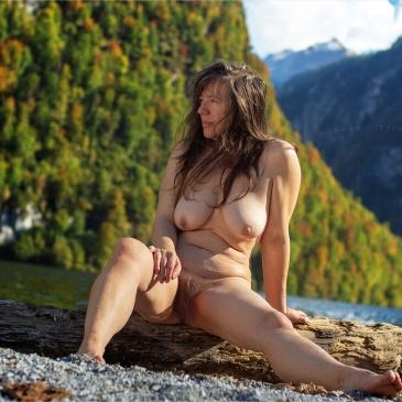 Nackte Frau sitzt am Königsee