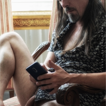 Nackter Mann im Sessel mit Handy