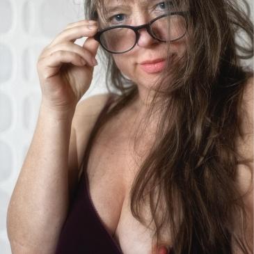 halbnackte frau mit brille und brust