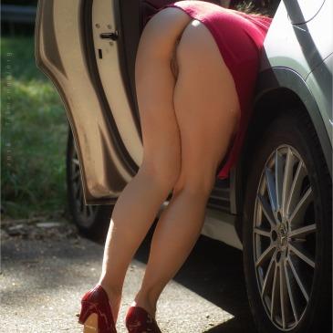 halbnackte frau bückt sich ins auto