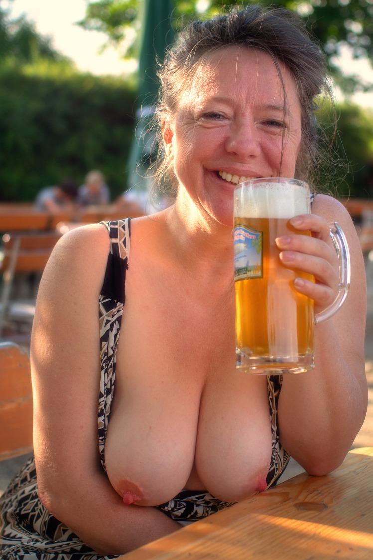 halbnackte Frau im Biergarten zeigt ihre Brüste