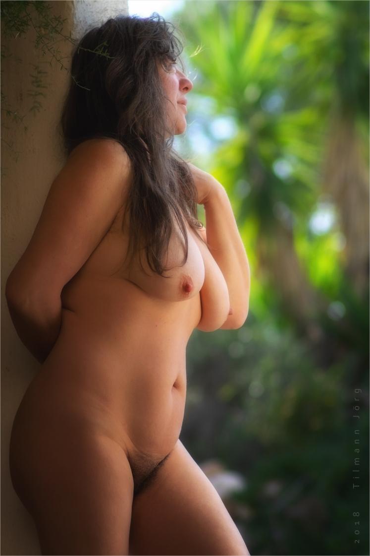 Nackte Frau im Türrahmen