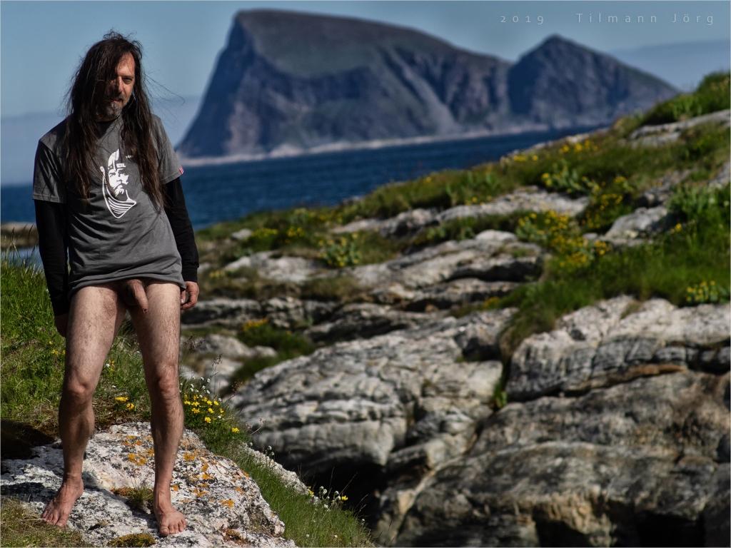 nackter Mann steht auf Felsen auf Sommarøy