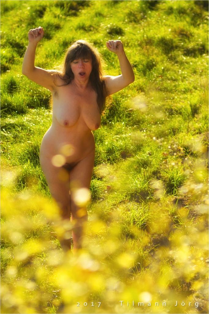 Nackte Frau tanzt in einer Wiese