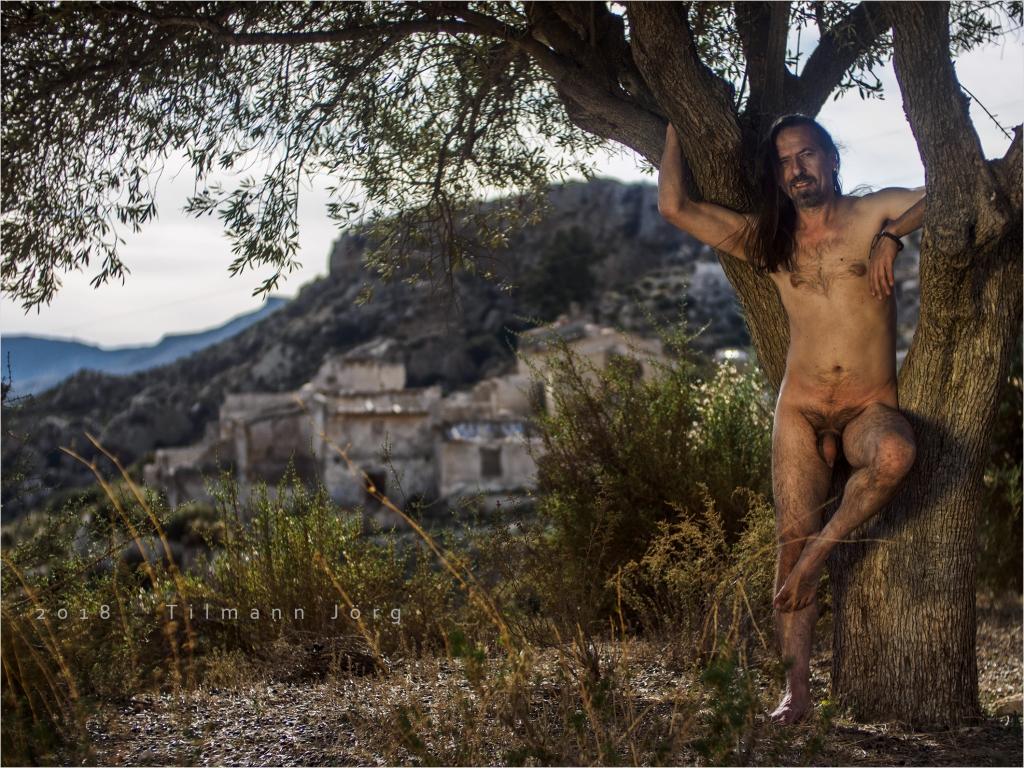 Nackter Mann unter Olivenbaum