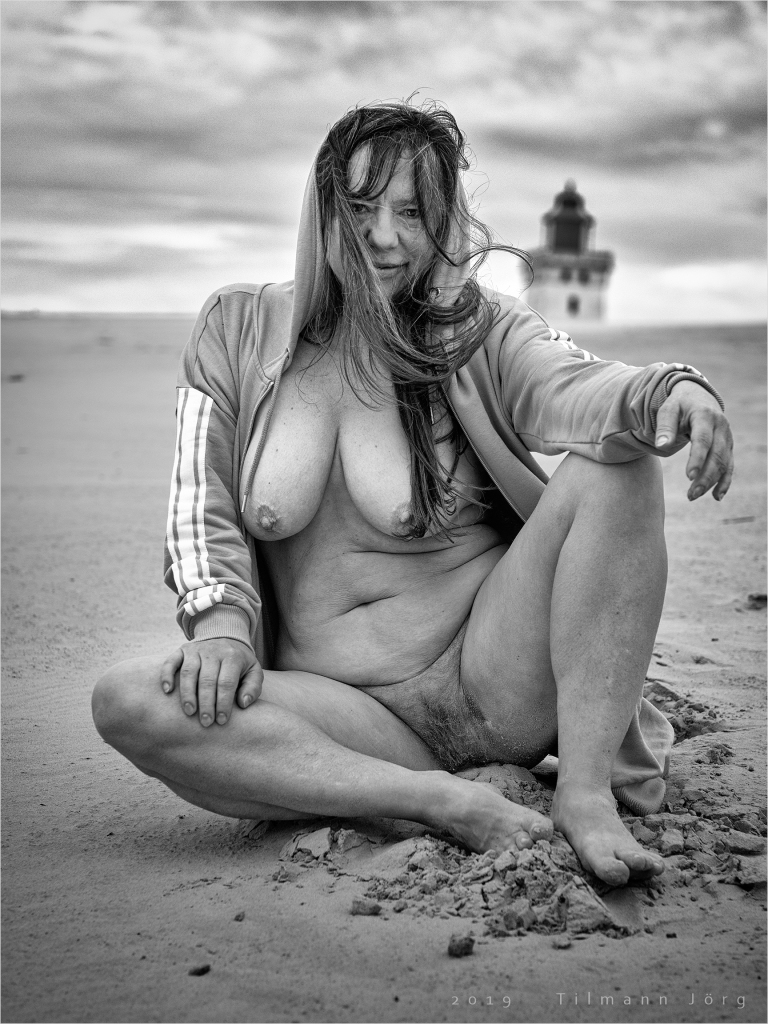 Frau sitzt nackt auf einer Sanddüne