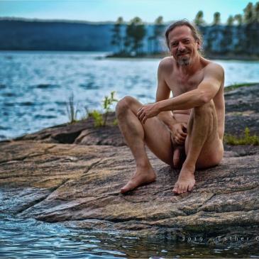 nackter mann sitzt an einem see in schweden
