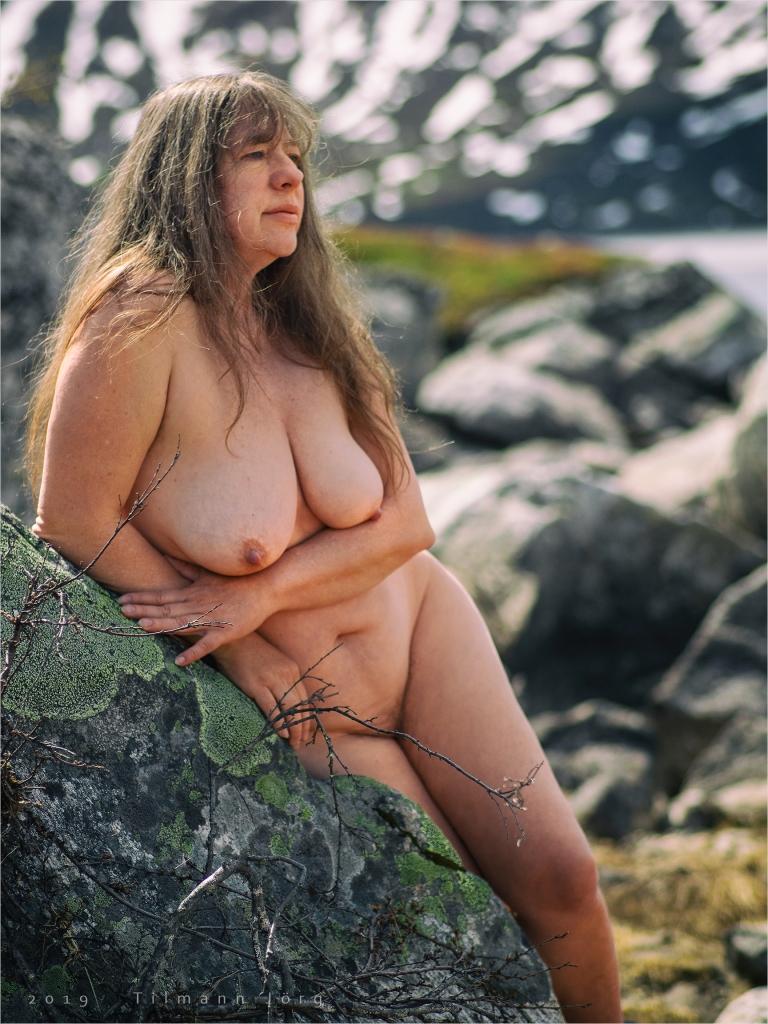 nackte Frau lehnt an einem Felsen in der Arktis