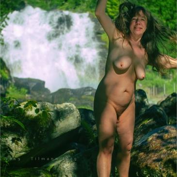 Nackte Frau posiert vor einem Wasserfall