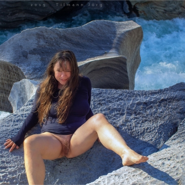 nackte Frau liegt auf einem Marmorfelsen vor reißendem Fluss