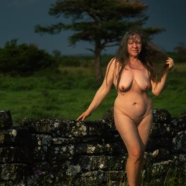 mackte Frau vor dunklem Himmel