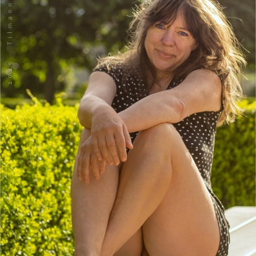 Frau sitzt auf einer Bank im Schlossgarten und zeigt ihre Möse