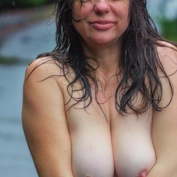 Frau mit bloßen Brüsten im Regen