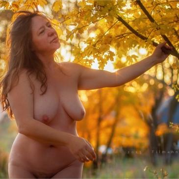 nackte frau unter einem Baum im Herbstlaub