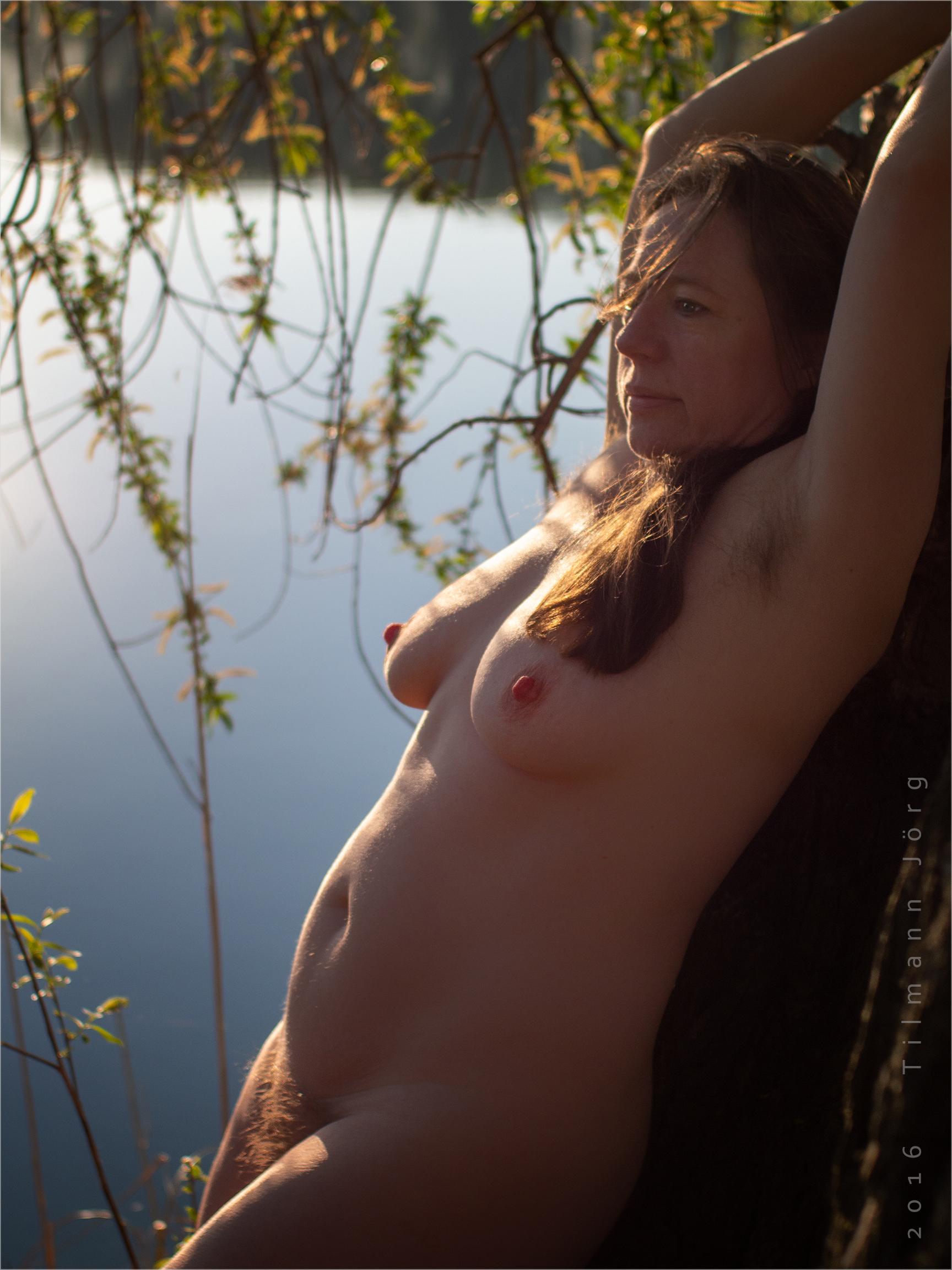 nackte Frau am Seeufer lehnt an einem Baum