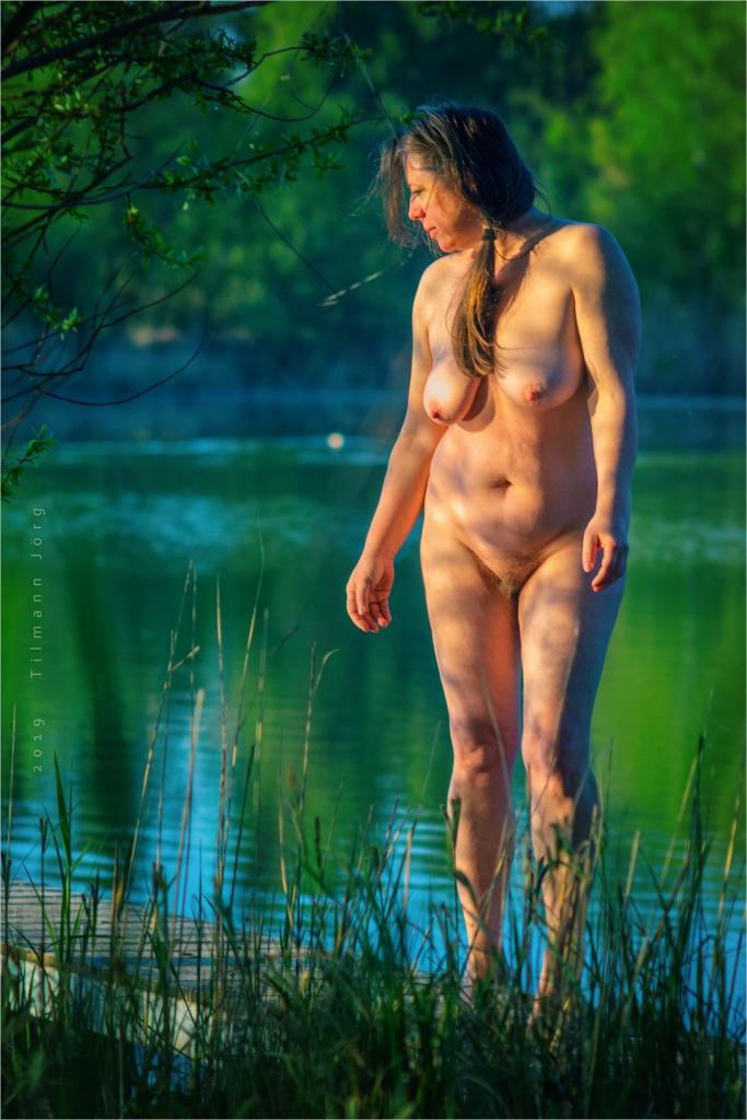 nackte frau auf einem Steg im See