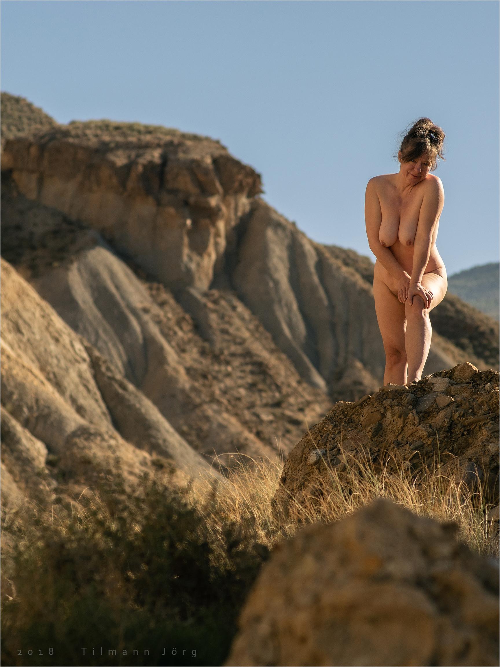 nackte frau steht auf einem hügel in der wüste