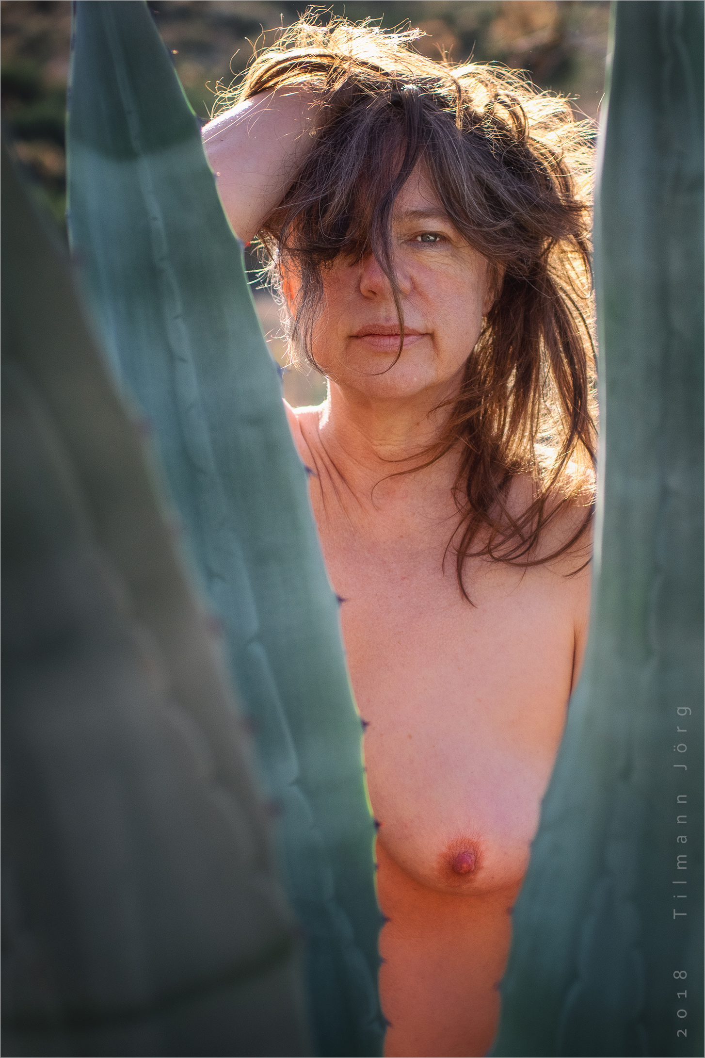 nackte frau hinter einer agave
