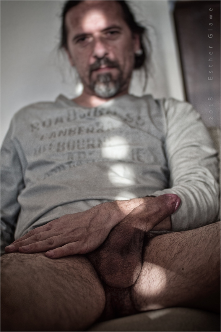 Mann ohne Hosen sitzt vor der Kamera und zeigt seinen Schwanz und die Hoden