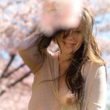 Frau inmitten rosa Kirschblüten zeigt eine Brust