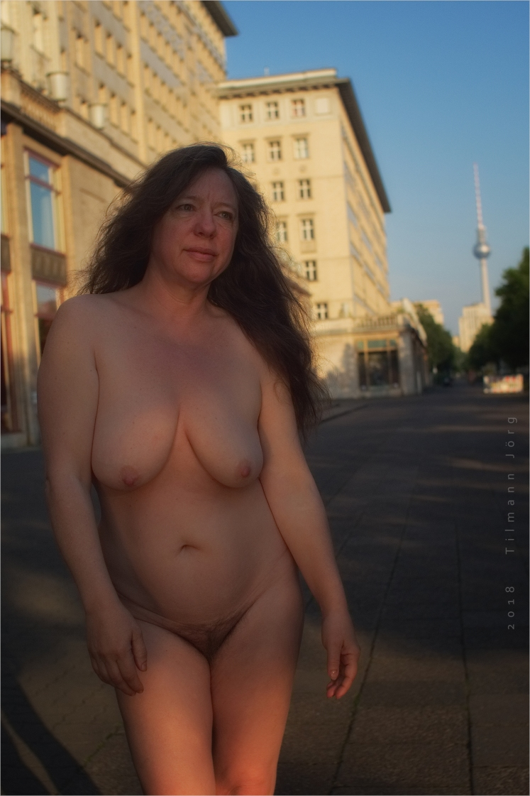 Nackte Frau steht an der Karl-Marx-Allee