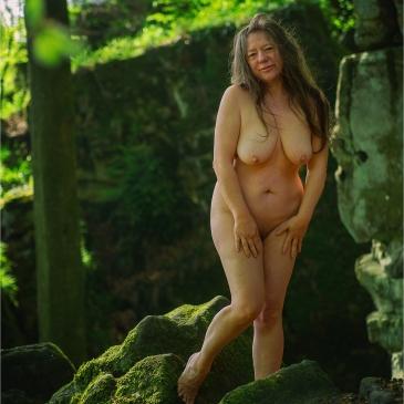 nackte Frau steht im Wald
