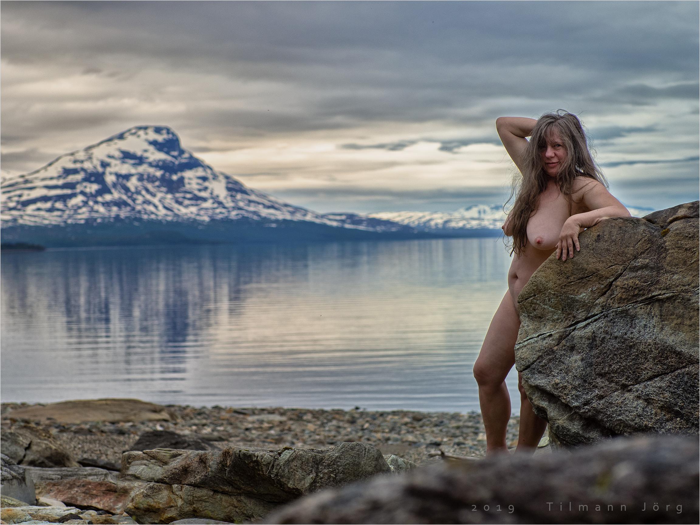 nackte frau vor einem arktischen see
