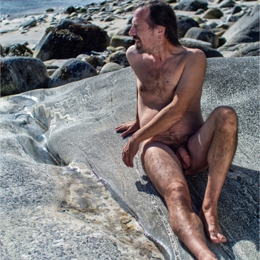nackte mann liegt auf einem felsen am meer